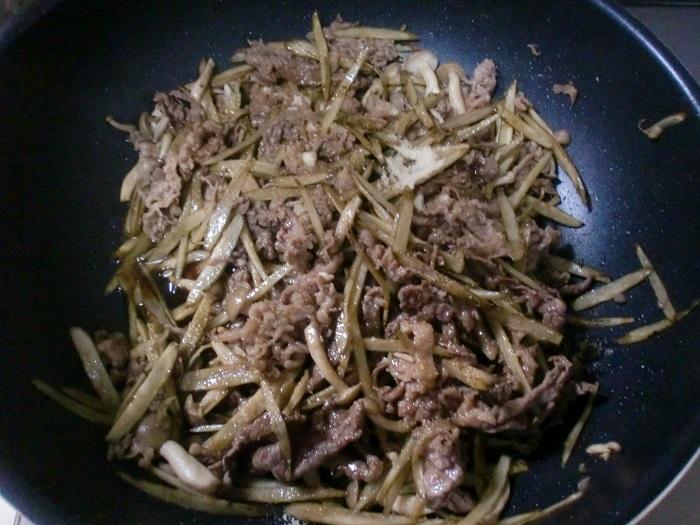 炒めた牛肉にしめじとごぼうを入れて炒め、最後に調味料を入れて炒める