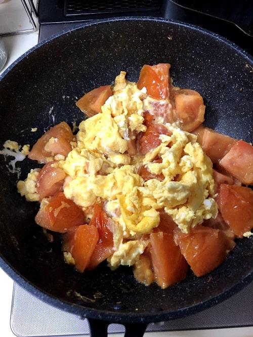 皿に移していたトロトロ卵をトマトと合わせて、鶏がらスープを入れて全体を軽く炒めて出来上がり。